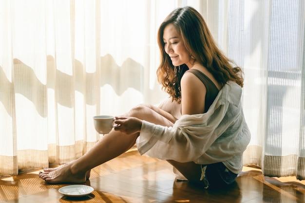 Uma linda mulher asiática sentada e segurando uma xícara de café quente para beber no chão pela manhã