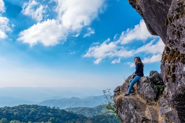 Uma linda mulher asiática sentada em um penhasco com vista para as montanhas e o céu azul
