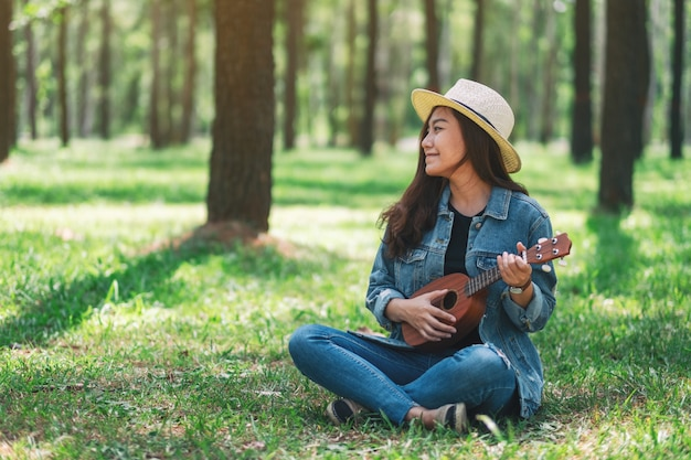 Uma linda mulher asiática sentado e tocando ukulele no parque