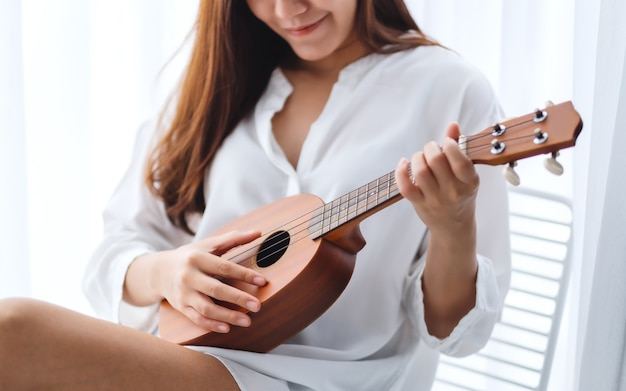 Uma linda mulher asiática sentado e tocando ukulele no quarto