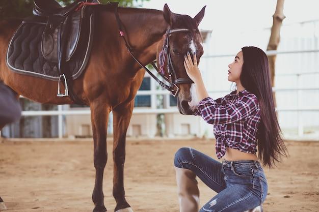Uma linda mulher asiática tailandesa com cabelo comprido e uma camisa tartan e jeans, ela está ajoelhada e acariciando a cabeça de um cavalo com amor.