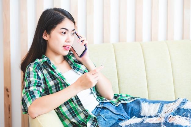 Uma linda mulher asiática tailandesa em uma camisa xadrez, ela está falando no celular no sofá.
