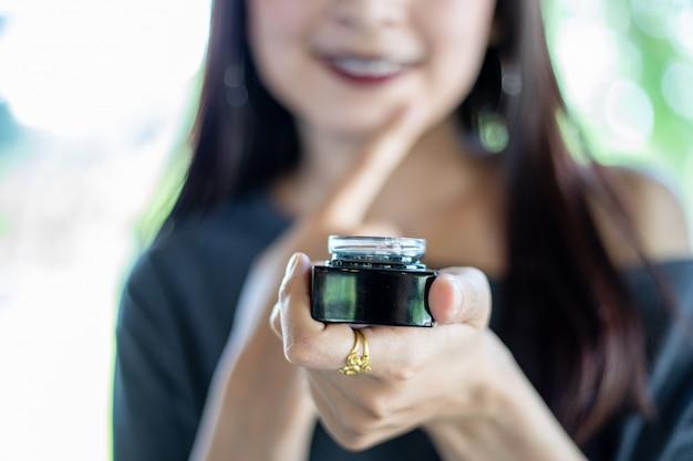 Uma linda mulher asiática usando um produto de cuidado de pele, hidratante ou loção cuidando de sua tez seca. creme hidratante nas mãos femininas.