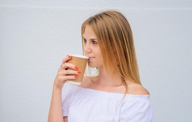 Uma linda mulher bebendo café para viagem. garota bebe café expresso, café com leite, cappuccino em copo de papel.