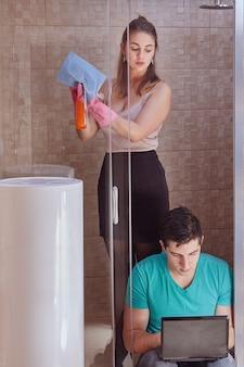 Uma linda mulher branca em roupas sensuais lava o chuveiro e observa um jovem sentado nas proximidades e usando o laptop.