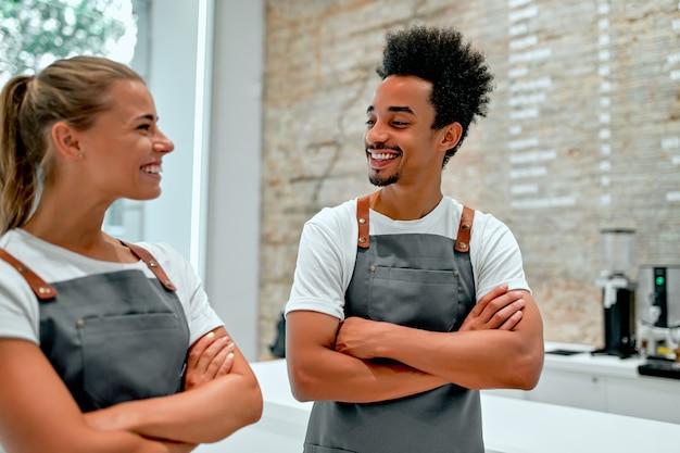 Uma linda mulher caucasiana e um atraente barista africano, vestido com um uniforme de avental, estão de braços cruzados em uma cafeteria.