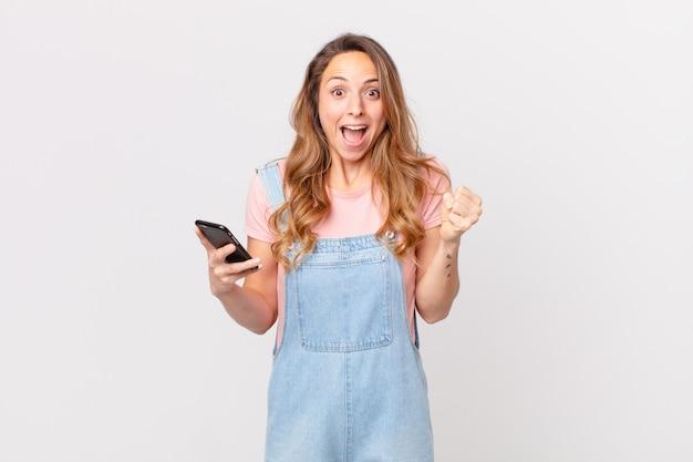 Uma linda mulher chocada, rindo e comemorando o sucesso e segurando um smartphone