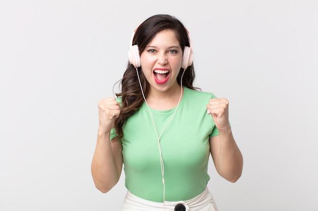 Uma linda mulher chocada, rindo e comemorando o sucesso ouvindo música com fones de ouvido