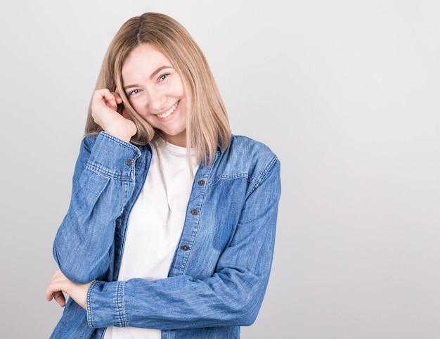 Uma linda mulher com cabelos loiros em uma camiseta branca e uma camisa jeans fica envergonhada, sorrindo fofo, com a mão perto do rosto.