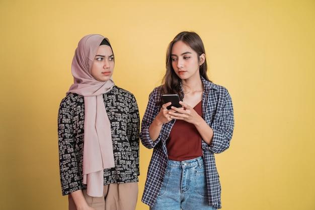 Uma linda mulher com confiança usando um telefone celular e uma mulher com véu ao lado dela olhando com desconfiança