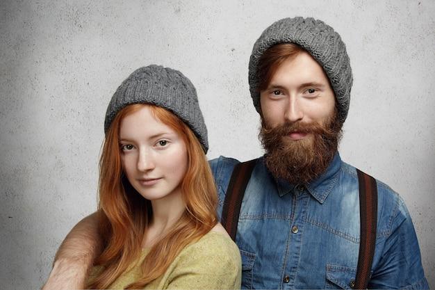Uma linda mulher com longos cabelos ruivos e um homem bonito vestido com roupas de inverno, isolado contra a parede