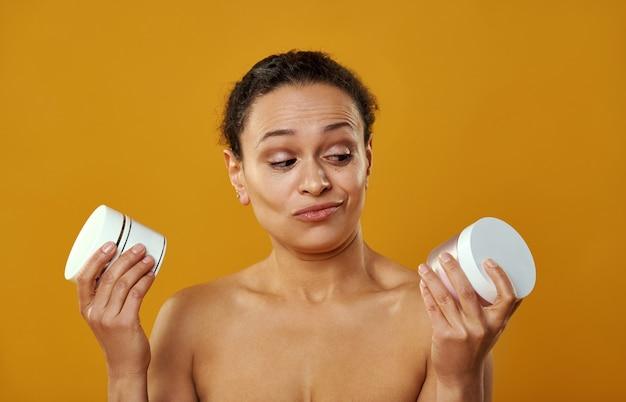 Uma linda mulher com o rosto enrugado ao escolher potes de cremes isolados em fundo amarelo