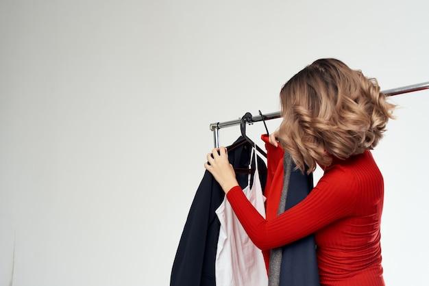Uma linda mulher com óculos experimentando emoções de shopaholic em uma loja de roupas