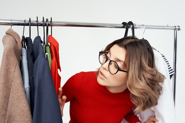 Uma linda mulher com óculos experimentando roupas shopaholic fundo claro