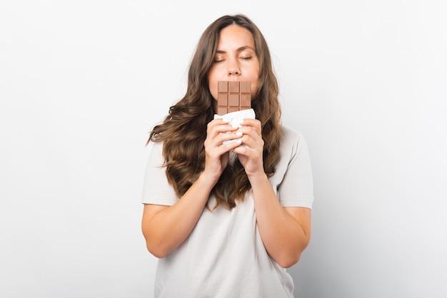 Uma linda mulher com os olhos fechados está segurando uma barra de chocolate na frente dos lábios.
