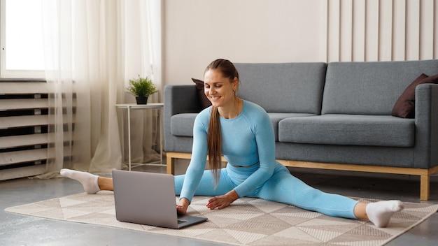 Uma linda mulher com um agasalho de treino azul está se espreguiçando em casa na frente de um laptop. ela se senta em uma corda transversal.
