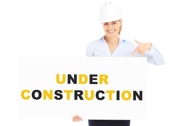 Uma linda mulher com um capacete mostrando um banner com a inscrição em construção