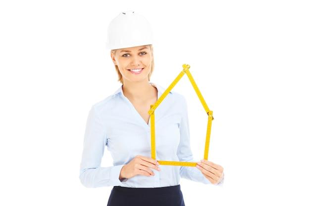 Uma linda mulher com um capacete mostrando uma casa sobre um fundo branco