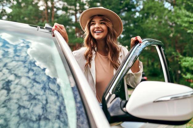 Uma linda mulher com um chapéu fica perto do carro no fundo da floresta. compra, aluguel de carro. descanse na natureza, fim de semana.