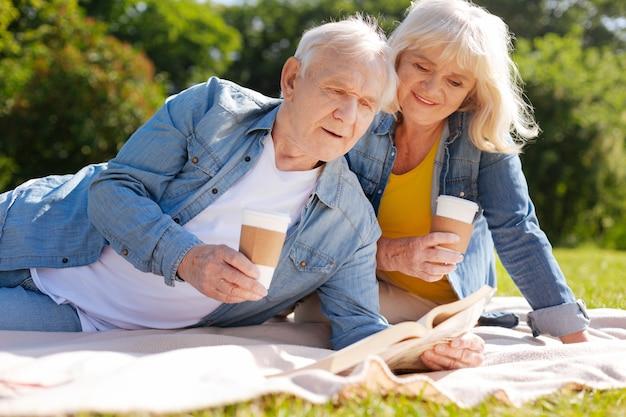 Uma linda mulher com um sorriso no rosto e segurando o copo de papel na mão direita enquanto está sentada atrás do marido