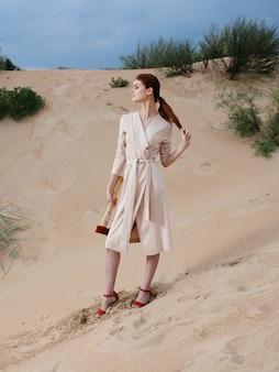 Uma linda mulher com um vestido de verão e sapatos vermelhos com um machado nas mãos
