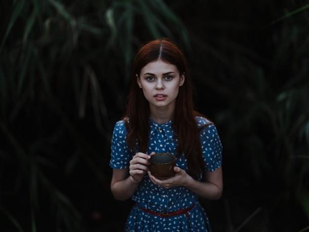 Uma linda mulher com um vestido vermelho, posando com a natureza do mato verde