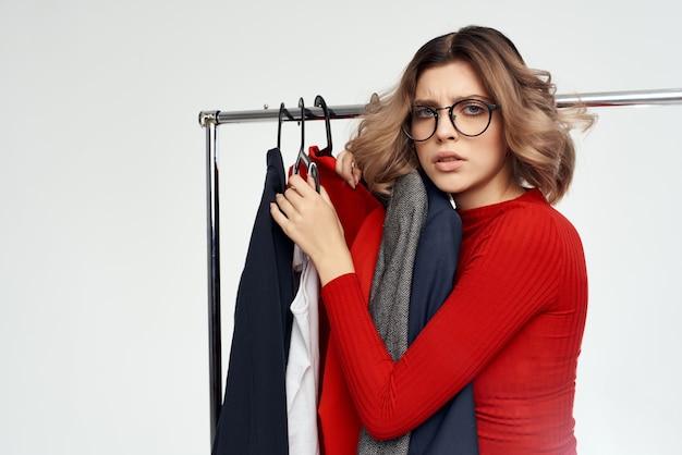 Uma linda mulher com uma jaqueta vermelha perto das emoções do varejo de guarda-roupa
