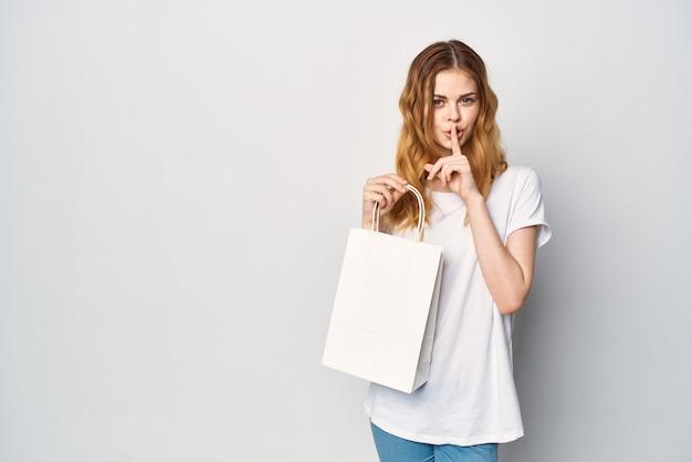 Uma linda mulher com uma sacola de compras de camiseta branca nas mãos