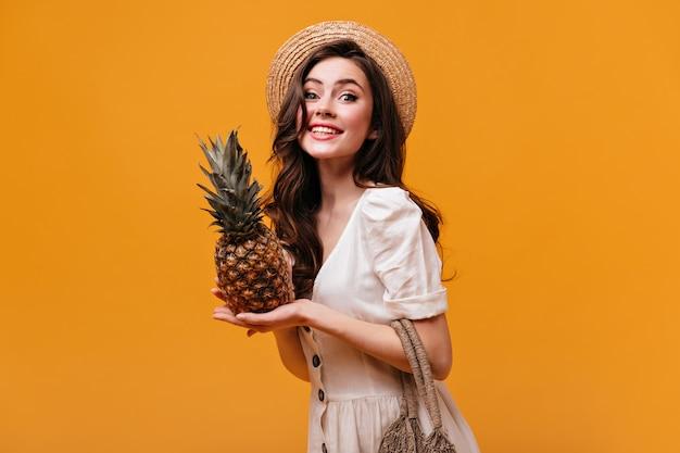 Uma linda mulher com vestido de algodão olha para a câmera com um sorriso e poses com abacaxi em fundo isolado.