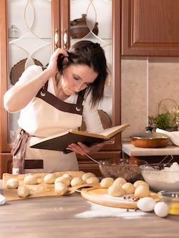 Uma linda mulher cozinhando tortas na cozinha em casa para a família dela. ela olha para o livro de receitas