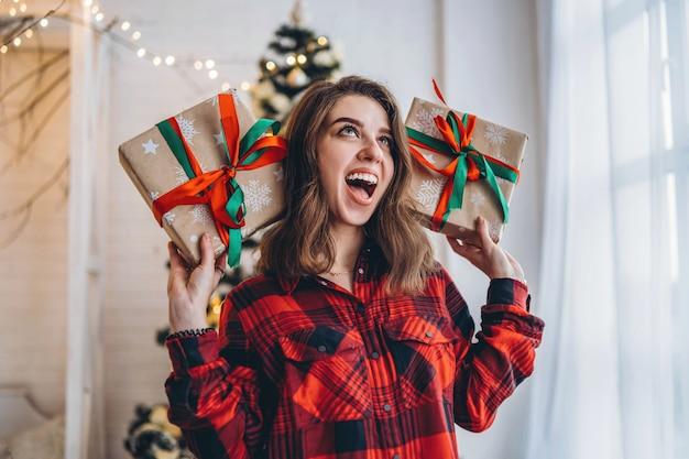 Uma linda mulher de camiseta e meias andando em casa com uma caixa de presente de natal