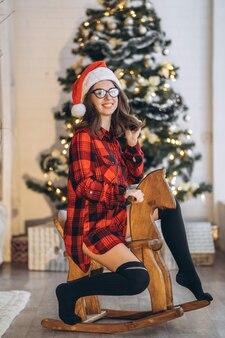 Uma linda mulher de camiseta e meias divirta-se andando no brinquedo do cavalo de balanço de madeira