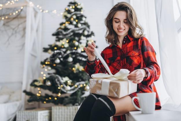 Uma linda mulher de camiseta e meias sentada no parapeito da janela com uma caixa de presente de natal