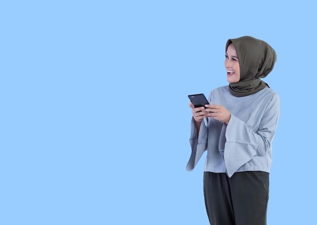 Uma linda mulher de hijab segurando o telefone com expressões sorridentes e surpresas