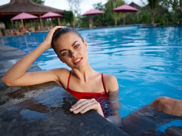 Uma linda mulher de maiô vermelho está encostada no ladrilho da piscina e tocando a cabeça com a mão