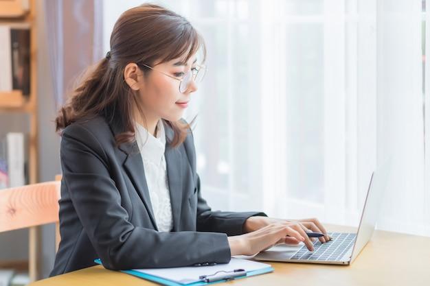 Uma linda mulher de negócios asiático. uma mulher tailandesa sorri e imprime documentos usando um caderno em uma mesa de madeira no escritório pela manhã.
