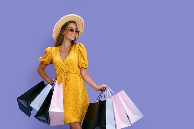Uma linda mulher de óculos escuros e chapéu segurando sacolas de compras coloridas no conceito de vendas de fundo roxo