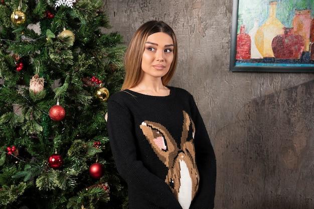 Uma linda mulher de suéter quente posando e desviando o olhar, perto de árvore de natal. foto de alta qualidade