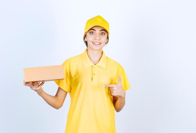 Uma linda mulher de uniforme amarelo apontando para uma caixa de papel artesanal marrom.