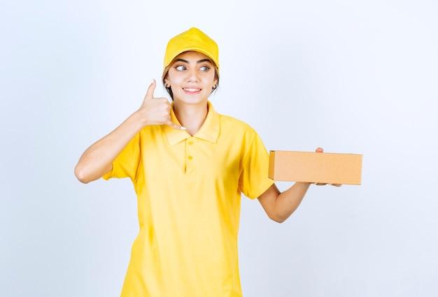Uma linda mulher de uniforme amarelo com uma caixa de papel artesanal marrom fazendo sinal de chamada.