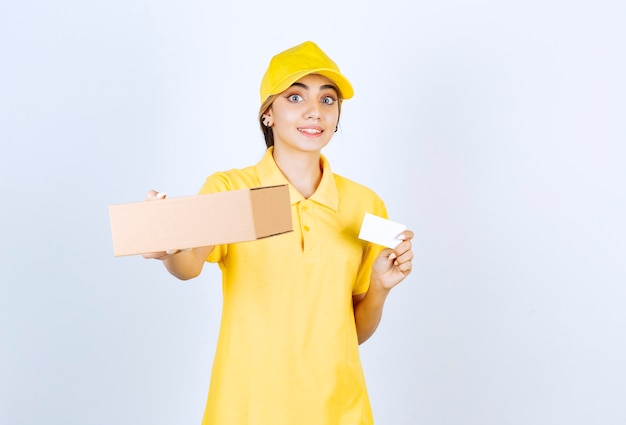 Uma linda mulher de uniforme amarelo segurando uma caixa de papel artesanal em branco.