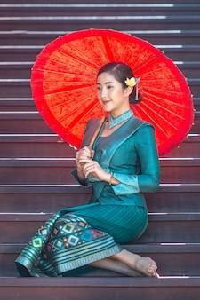 Uma linda mulher do laos vestida com trajes tradicionais do laos. estava sentado segurando um guarda-chuva vermelho na escada da casa de madeira