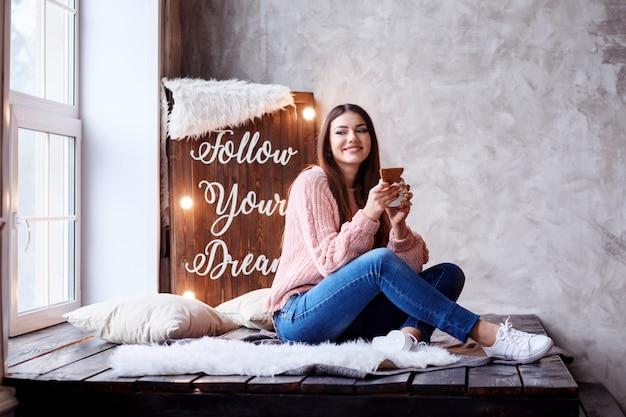Uma linda mulher é comer biscoito e beber chá ou café em casa ao lado da janela. siga o painel de luz dos seus sonhos.