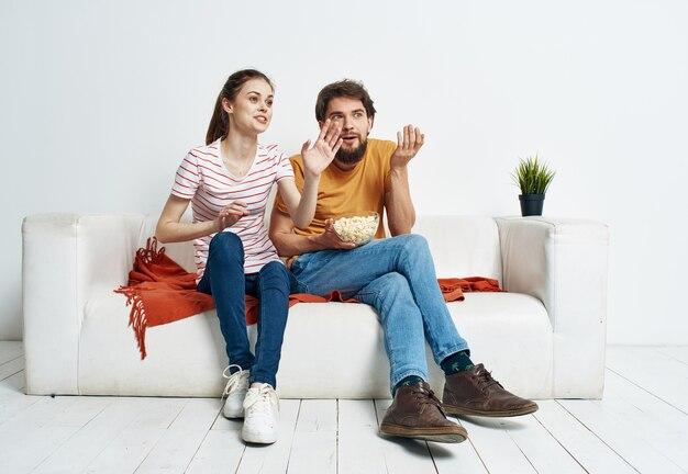 Uma linda mulher e um homem barbudo assistindo tv no sofá dentro de casa
