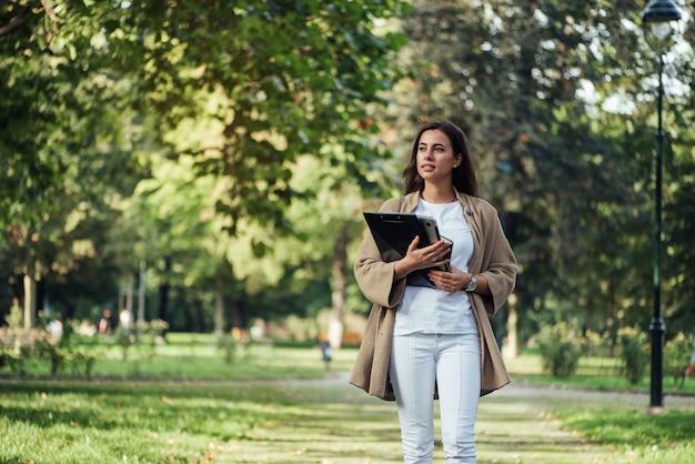 Uma linda mulher em pé com o caderno de pasta e o laptop no fundo do parque de verão