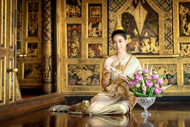 Uma linda mulher em traje nacional tailandês durante o período ayuthaya estava sentada em uma série de guirlandas.