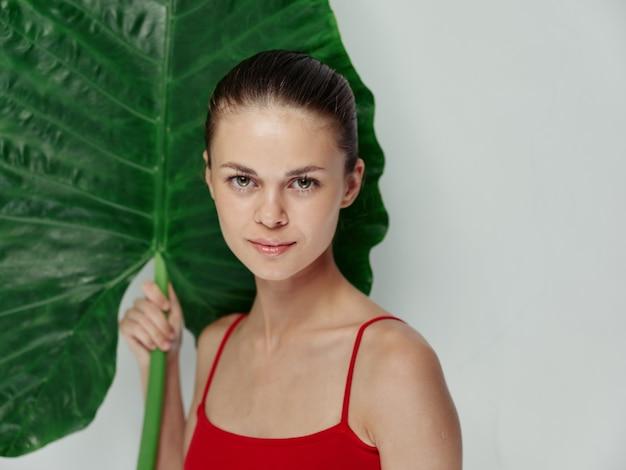 Uma linda mulher em um maiô vermelho segurando uma folha de palmeira em suas mãos.