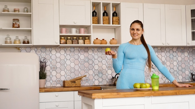 Uma linda mulher em um terno azul está de pé na cozinha, sorrindo e segurando uma maçã verde. o conceito de esportes e perda de peso em casa.