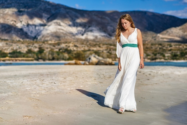 Uma linda mulher em um vestido branco caminhando na praia de elafonisi