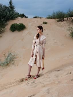 Uma linda mulher em um vestido de verão e sapatos vermelhos com um machado nas mãos.